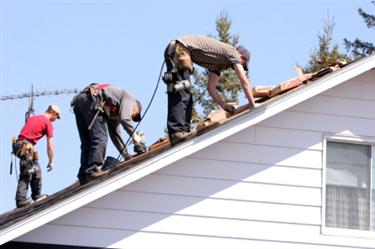 Roof Installation in Placedo TX. Three roofers laying new shingle on a roof in Placedo.
